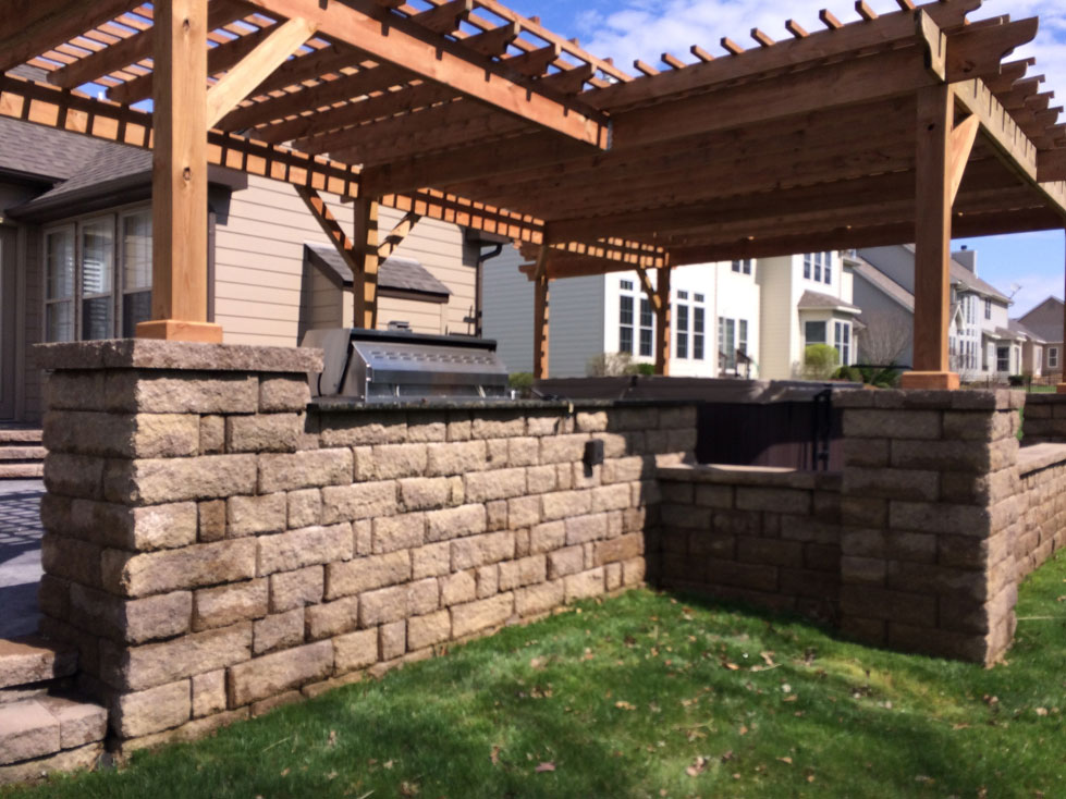 A pergola sits atop interlocking concrete blocks in a backyard in St. Louis