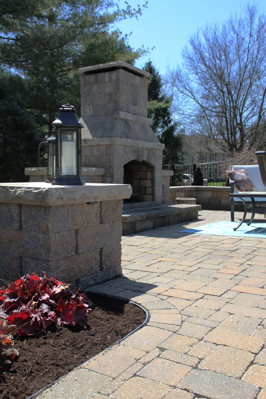 A stone outdoor fireplace is flanked by candles in St. Louis