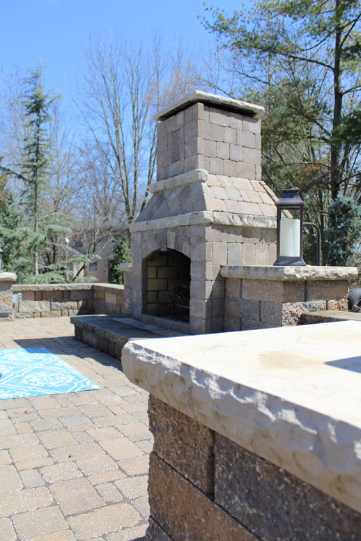A side view of a beautiful stone fireplace designed by Tennant Lawn Service