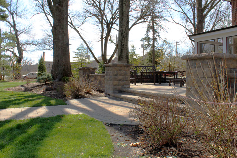 A walkway leads to steps and a patio in a backyard in St. Louis