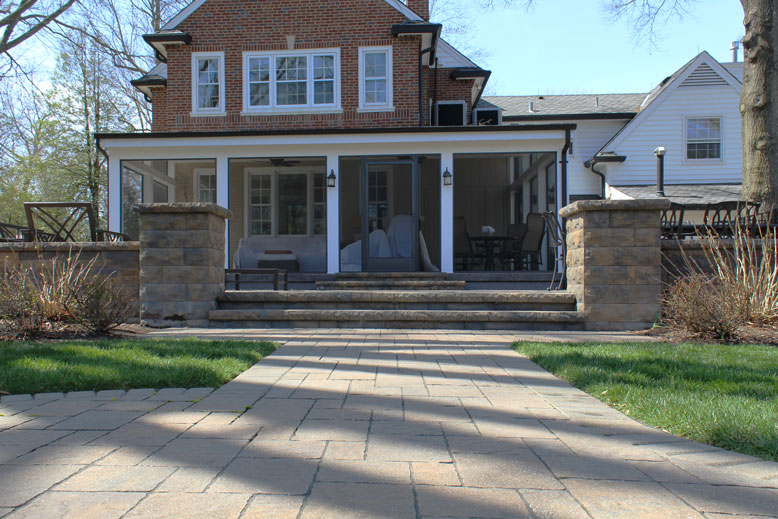 A concrete walkway leads to steps and an enclosed porch in St. Louis