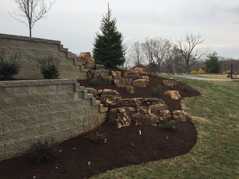 A retaining wall of natural and interlocking stone by Tennant Lawn Service
