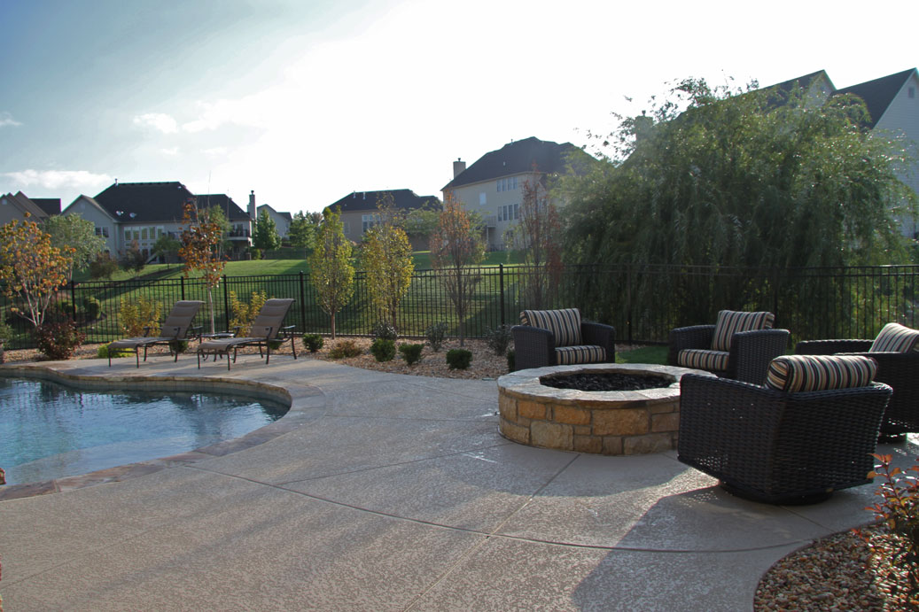 A patio, firepit and gardens surrounding a pool in St. Louis