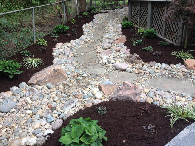 A dry river bed curves through a sideyard in St. Louis