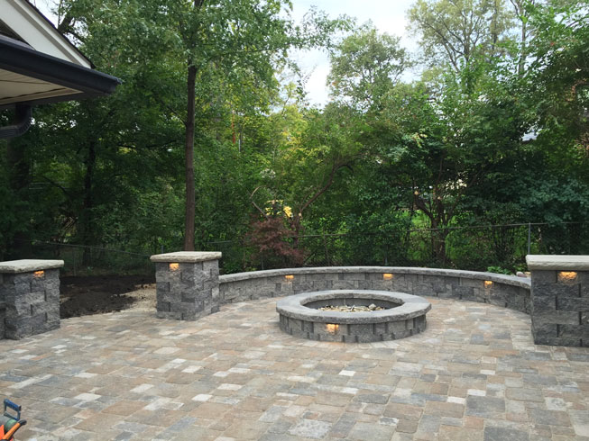 A concrete patio with a firepit and seating wall designed by Tennant Lawn Service, Inc.