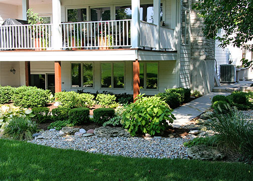 A backyard featuring a garden designed by Tennant Lawn Service, Inc.